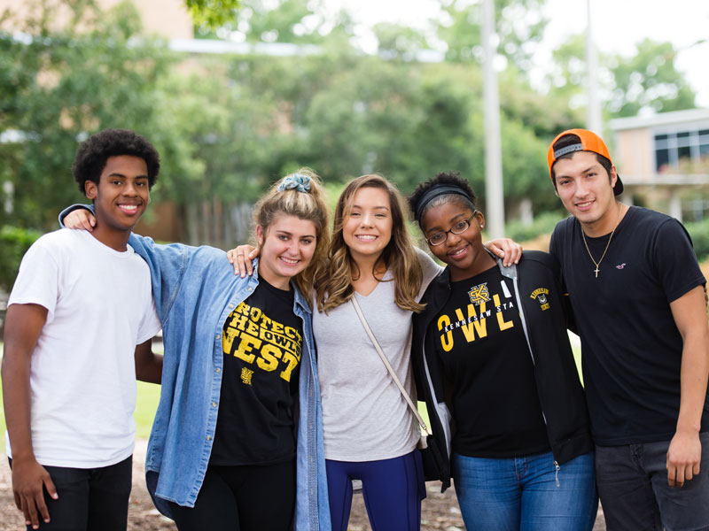 A group of five students posing together at the Kennesaw Campus.