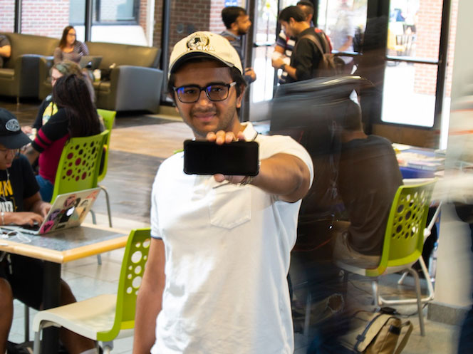 Devan Patel holding up a smart phone.