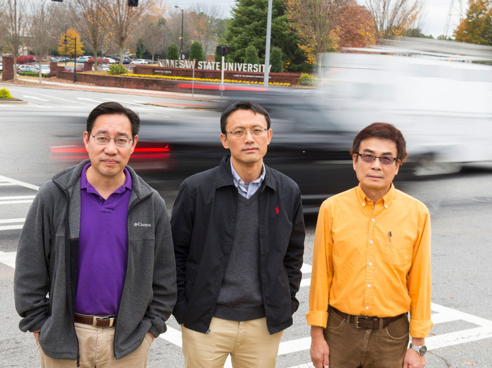 All three KSU faculty standing in front of moving cars.