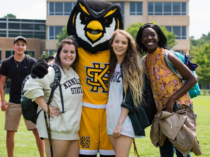 Students posing with Scrappy the Owl on the Campus Green.