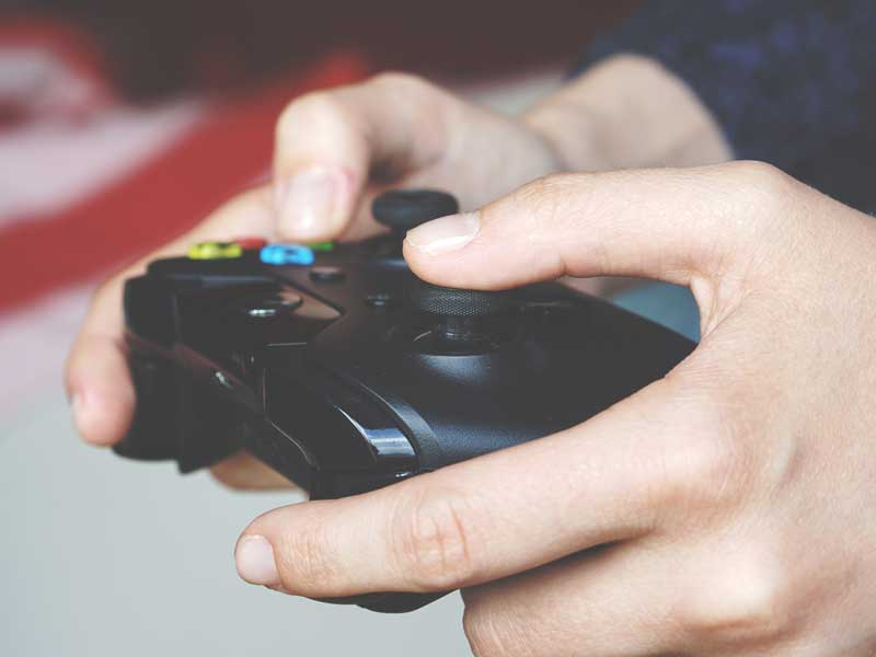 A pair of hands holding an Xbox controller.