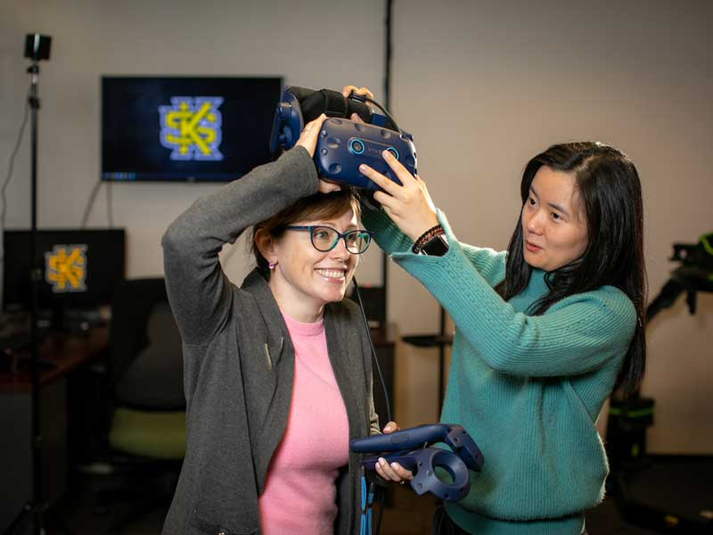 A student putting a VR headset on a tester.